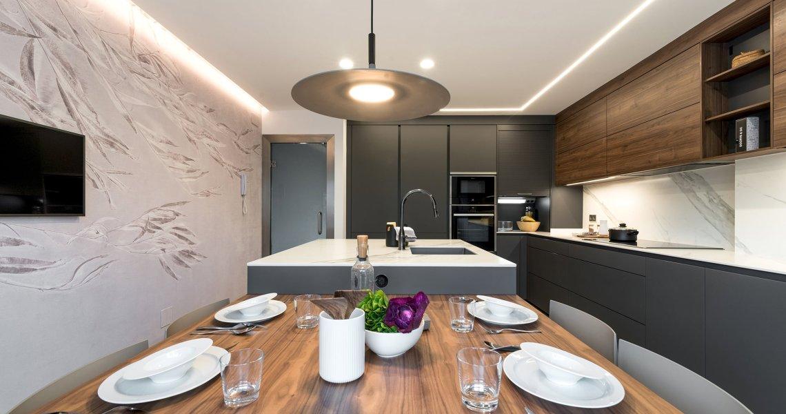 Cocina gris con isla, papel pintado Glamora y lámpara Foscarini