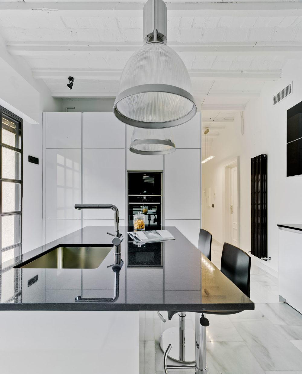 Encimera oscura en cocina blanca moderna